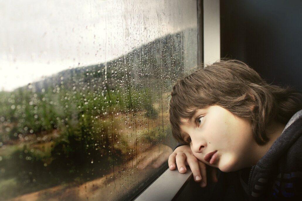 Niño en ventana de PVC viendo llover